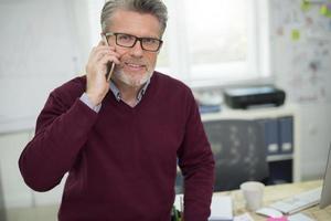Porträt des Mannes, der am Telefon spricht foto