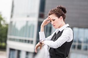 müde oder depressive Geschäftsfrau draußen foto
