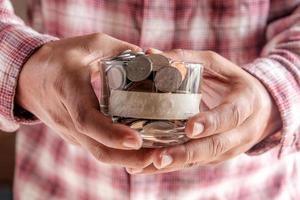 Mann, der Geldglas mit Münzen nah oben hält foto