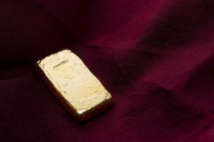 Goldbarren auf roter Seide foto
