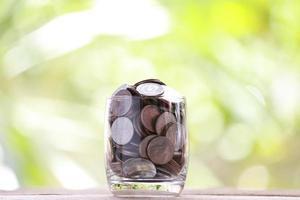 Silbermünze in Glas wird auf einen Holzboden gelegt. foto