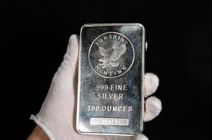 100 Unzen Silberbarren Sonnenschein Minze Hand gehalten foto