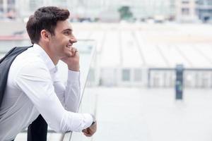 hübscher junger Geschäftsmann benutzt Telefon für Kommunikation foto