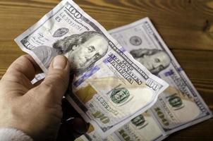 zerknitterte 100-Dollar-Banknoten-Nahaufnahme in der Hand über 100-Dollar-Scheine. foto