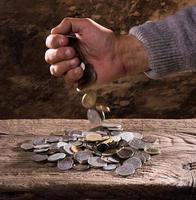Hände des kaukasischen Mannes und Stapel alter Münzen foto