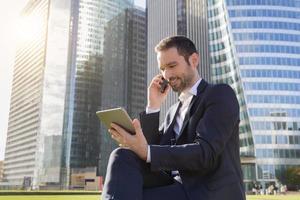 Geschäftsmann mit einem Telefon und einem digitalen Tablet