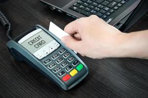 Mann zahlt mit Kreditkarte. Plastikkarte durch Terminal wischen foto