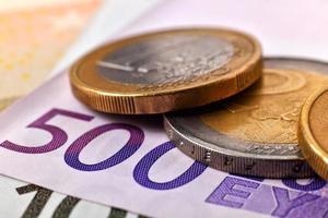 Münzen und fünfhundert Euro Banknoten foto
