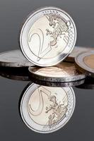 zwei Euro-Münzen (auf dunklem Spiegelhintergrund)