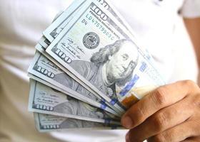 Mann, der einen Spread von Bargeld anzeigt foto