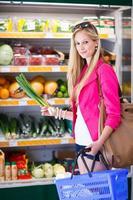 schöne junge Frau, die in einem Supermarkt einkauft