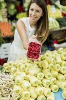 junge Frau, die Himbeeren auf dem Markt kauft foto