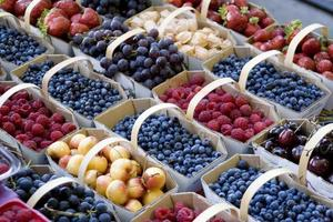 gefüllte Körbe mit gemischten frischen Früchten nebeneinander