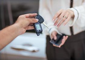 männliche Hand, die Autoschlüssel zur weiblichen Hand gibt.