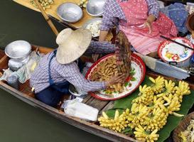 Frau, die Lebensmittel auf einem der schwimmenden Märkte Thailands handelt.