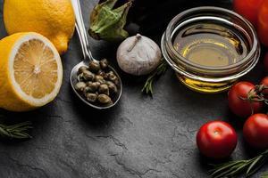 Olivenöl mit Gemüse, Zitrone und Kapern