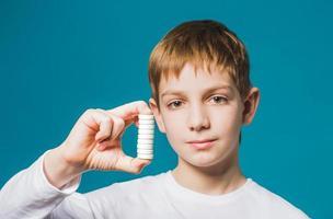 Nahaufnahmeporträt eines Jungen, der Pillen hält foto