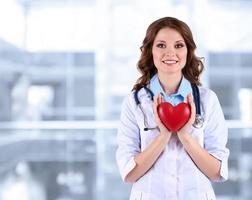 junger schöner Arzt, der Herz auf Krankenhaushintergrund hält foto