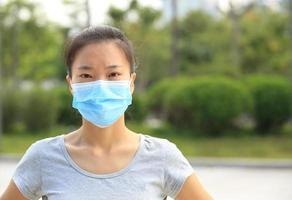 junge Frau, die Gesichtsmaske auf Stadt trägt foto