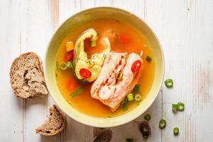 Lachssuppe mit Brot serviert foto