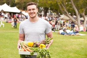 Mann mit frischen Produkten auf dem Bauernmarkt im Freien gekauft foto