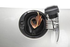 Konzept Banknoten in Benzin Nachfüllleitung foto