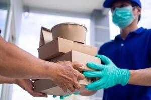 Der Mitarbeiter der Lebensmittellieferung trägt eine Maske und Handschuhe vor der Haustür des Kunden, um das Mittagessen zu liefern foto