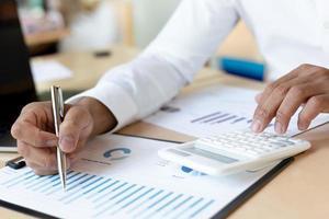 Geschäftsmann, der finanzielle Vermögenswerte am Schreibtisch kartiert foto