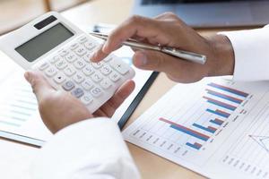 Geschäftsmann, der am Schreibtisch sitzt und finanzielle Gewinne berechnet foto