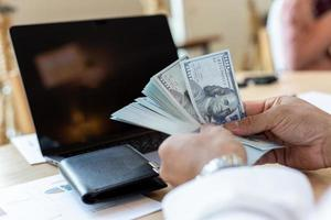Geschäftsmann behandelt Geld bei der Arbeit, um Abschlüsse zu analysieren foto