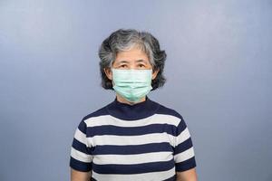eine ältere asiatische Frau, die chirurgische Maske auf festem Hintergrund trägt