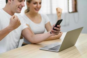 Ein junges kaukasisches Paar, das zu Hause Technologie einsetzt foto