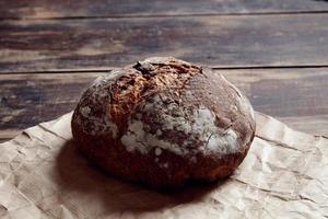 rundes Brot von oben auf einem Holztisch beiseite foto