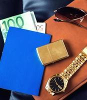 Reiseaccessoire, Reisepass, Geld, goldene Uhr, Sonnenbrille und Feuerzeug