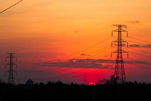 Hochspannungspfosten bei Sonnenuntergang foto