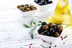 grüne und schwarze Oliven in der Schüssel auf weißem hölzernem Hintergrund foto