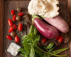 reife Aubergine mit Tomaten und Salz auf einem hölzernen Hintergrund