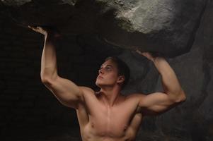 starker Mann, der Stein hält foto