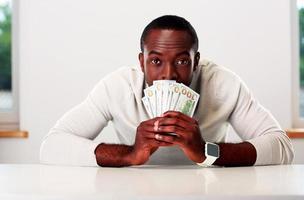 Porträt des afrikanischen Mannes, der am Tisch sitzt foto