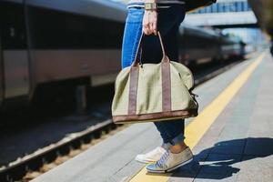Frau hält eine Tasche an einem Bahnhof foto