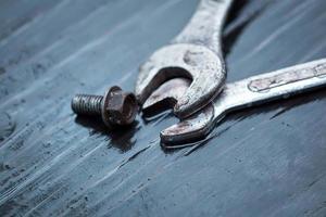 Schraubenschlüssel mit Schrauben oben auf Holztisch foto