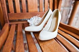 cremefarbene Hochzeitsschuhe der Braut auf Holzstuhl foto