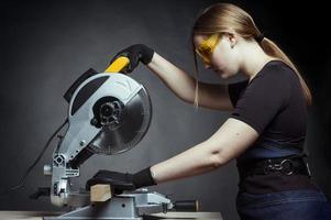 Frau mit einer kreisförmigen Scheibensäge foto