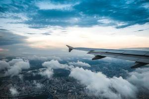 Wolken und Himmel durch das Fenster eines Flugzeugs gesehen