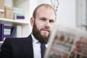 Porträt eines geschã¤ftsmann der eine Zeitung liest