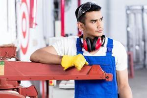 asiatischer Zimmermann mit elektrischer Säge in Werkstatt foto