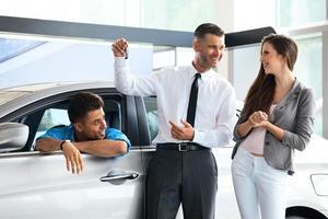 Verkäufer, der den Besitzern den Schlüssel vom neuen Auto gibt foto