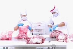 Metzger, der Fleisch auf dem Tisch schneidet foto