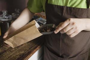 Verkäuferin, die Bestellung im Buch am Teeladen schreibt foto