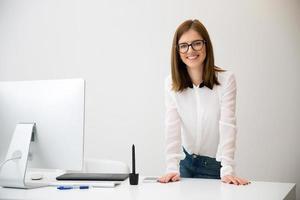 lächelnde Geschäftsfrau, die nahe ihrem Arbeitsplatz steht foto